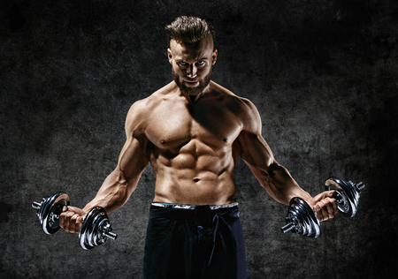 Powerful bodybuilder doing the exercises with dumbbells. Photo of strong male with naked torso on dark background. Strength and motivation. Zdjęcie Seryjne