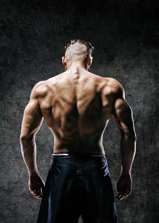 背面図。暗い背景に筋肉の男の裸の胴体。強度とモチベーション
