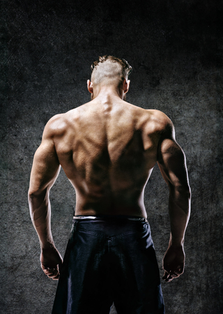 Back view. Naked torso of muscular man on dark background. Strength and motivation Banco de Imagens