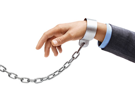 symbol victim: Mans hand in a suit in chains isolated on white background. Close up, concept against violence