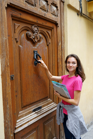 Young traveling girl standing near an old door. Travel in Spain. Фото со стока