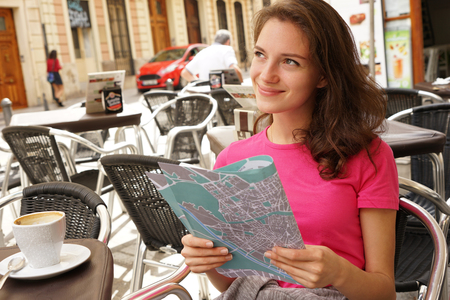 Young girl drinks a coffee. Photo of tourist with map sitting at table at cafe, outside. Travel in Spain.