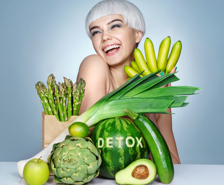 Happy young girl with an abundance of fruits and vegetables. Photo of smiling blonde girl on blue background. Healthy lifestyle concept