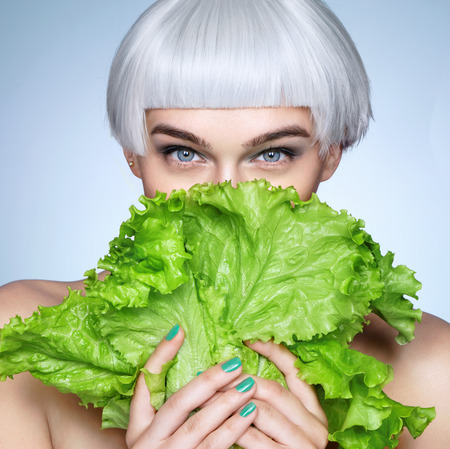 Pretty girl hiding behind a lettuce leaves. Photo of fashion blonde girl on blue background. Detox concept 스톡 콘텐츠