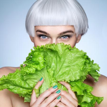 Pretty girl hiding behind a lettuce leaves. Photo of fashion blonde girl on blue background. Detox concept Standard-Bild