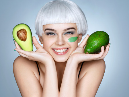 Happy smiling girl with green avocado. Photo of smiling blonde girl on blue background. Skin care and beauty concept.