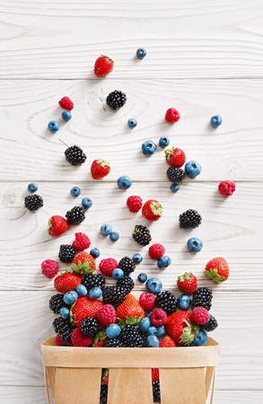 Explosion of different berries. Photo of strawberry, blueberry, blackberry, raspberry in basket on white wooden table. Top view. High resolution product. Reklamní fotografie - 89418010