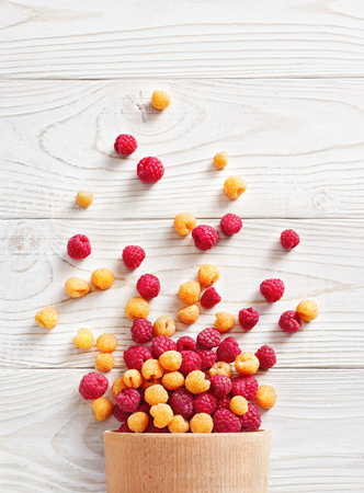 Raspberry explosion. Photo of raspberry in bowl on white wooden table. Top view. High resolution product.
