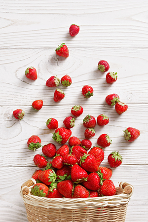 Strawberry explosion. Photo of strawberry in basket on white wooden table. Top view. High resolution product. 스톡 콘텐츠