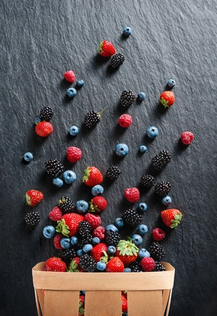 Explosion of different berries. Photo of strawberry, blueberry, blackberry, raspberry in basket on black slate. Top view. High resolution product. Stock Photo