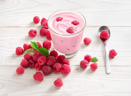 Yogurt with raspberry on white wooden table. Fresh yogurt. Healthy food concept. High resolution product.