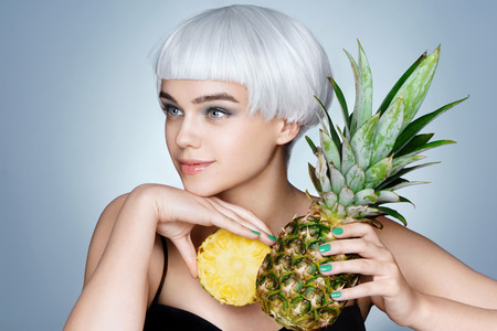 Happy young girl with pineapple. Photo of fashion blonde girl on blue background. Healthy lifestyle concept