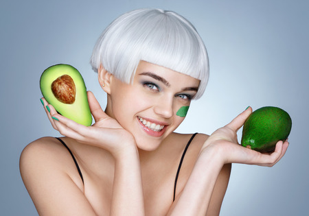 Happy girl with green avocado. Photo of smiling blonde girl on blue background. Skin care and beauty concept.