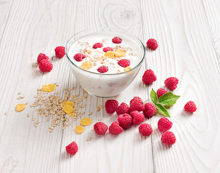 Bowl of homemade yogurt with muesli and fresh raspberry on wooden table. Fresh yogurt. Healthy food concept. High resolution product.