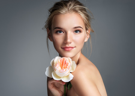 Beautiful girl with beautiful makeup. Photo of blonde girl with rose on grey background. Youth and skin care concept