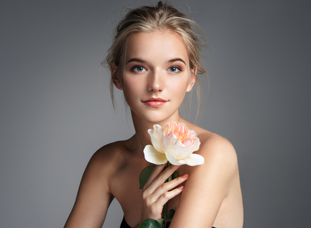 Charming young girl with perfect makeup. Photo of blonde girl with rose on grey background. Skin care concept 스톡 콘텐츠 - 90657649