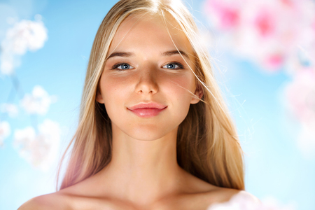 Beautiful blonde girl around spring flowers. Youth and skin care. Spring. Banco de Imagens