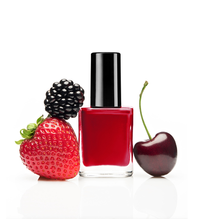 Red nail polish bottle with berries (blackberry, strawberry, cherry) on white background Imagens
