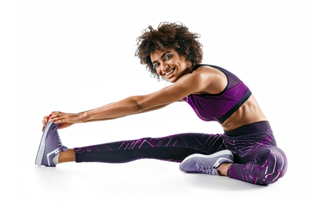 Sporty girl stretching her hamstrings. Photo of smiling african girl doing exercising on white background. Sports