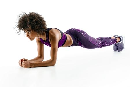Hermosa joven haciendo ejercicio tablón. Foto de la muchacha africana en silueta en el fondo blanco. Fitness y concepto de estilo de vida saludable