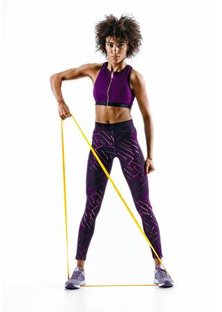 Atletisch meisje voert oefeningen uit met behulp van een weerstandsband. Foto van jong meisje dat op witte achtergrond wordt geïsoleerd. Kracht en motivatie Stockfoto