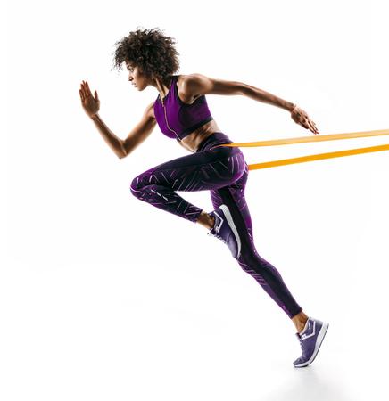 Starkes Mädchen in der Silhouette unter Verwendung eines Widerstandsbandes. Foto des jungen afrikanischen Mädchens führt Fitnessübungen lokalisiert auf weißem Hintergrund durch. Seitenansicht