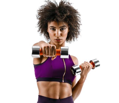 Garota esportiva fazendo exercícios de boxe, fazendo direto bate com halteres. Foto da menina africana no fundo branco. Força e motivação