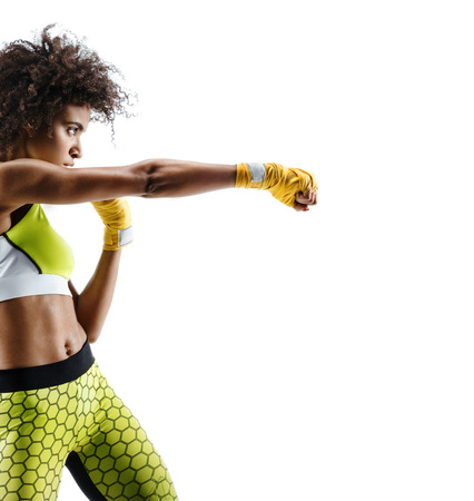 Boxer woman in yellow bandages making direct hit. Photo of sporty african woman during boxing on white background. Dynamic movement. Side view Stockfoto