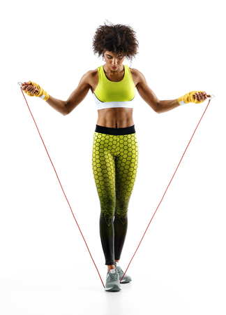Athletic girl with a jump rope on white background. Best cardio workout