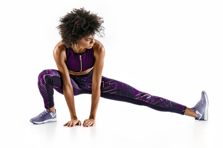 Beautiful young girl stretching her hamstrings. Photo of sporty girl doing exercising on white background. Sports Stockfoto
