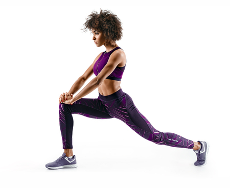 Fitness african girl doing stretching workout. Full length shot of young girl on white background. Stretching and motivation