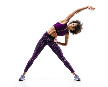 フィットネスエクササイズを行うスポーティな若い女性は、白い背景に隔離された腹筋。健康的な生活の概念。全長