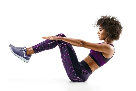 Bella ragazza facendo sit-up di esercizio fitness, addominali. Foto della ragazza africana in siluetta su fondo bianco. Fitness e concetto di stile di vita sano