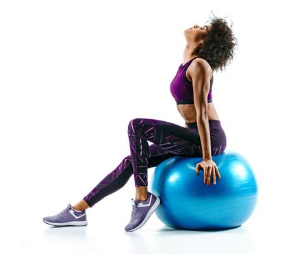 女の子は体操ボールの上に座って休んでいる。白い背景にスポーツウェアのスポーティなアフリカの女の子の写真。スポーツ