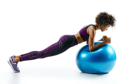 Sporty girl doing plank exercise on gymnastic ball. Photo of sporty african girl in sportswear on white background. Sports
