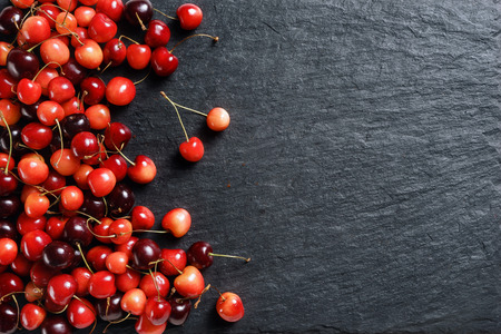 Fresh cherry on black slate. Copy space. Top view. High resolution product.