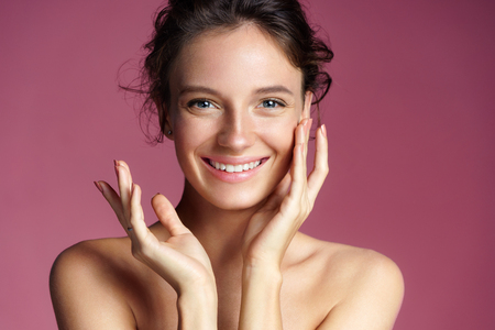 Young pretty girl with natural makeup on pink background. Beauty & Skin care concept 免版税图像