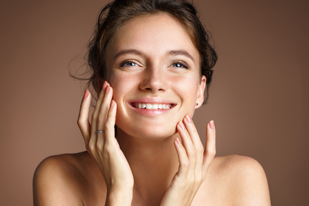 Attractive young girl touching her face on beige background. Beauty & Skin care concept Stock Photo