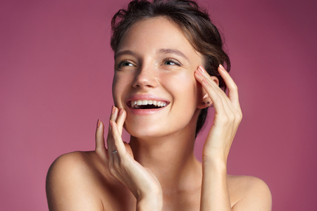 Young girl touching her healthy skin on pink background. Youth and skin care concept 免版税图像