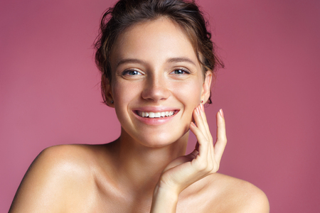 Beautiful young girl touching her perfect skin on pink background. Skin care concept Stock Photo