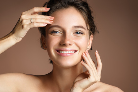 Charming woman with perfect skin on beige background. Beauty & Skin care concept 스톡 콘텐츠