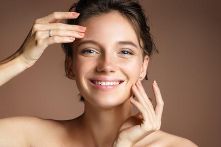 Charmante vrouw met perfecte huid op beige achtergrond. Schoonheid & huidverzorging concept Stockfoto