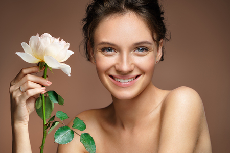 Beautiful smiling girl. Photo of young girl with rose on beige background. Beauty & Skin care concept