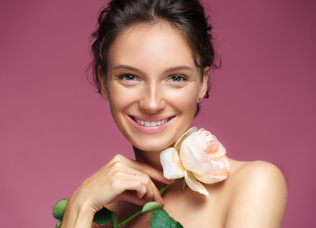 Beautiful girl with rose. Photo of happy brunette girl on pink background. Youth and skin care concept