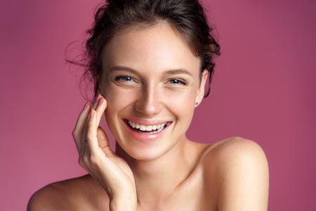 Jovem feliz tocando sua pele perfeita em fundo rosa. Conceito de beleza e cuidados com a pele Foto de archivo