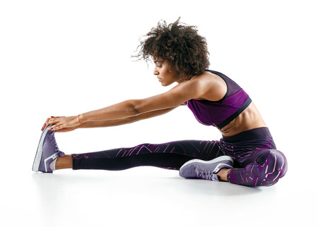 Photo of african girl doing exercising on white background.