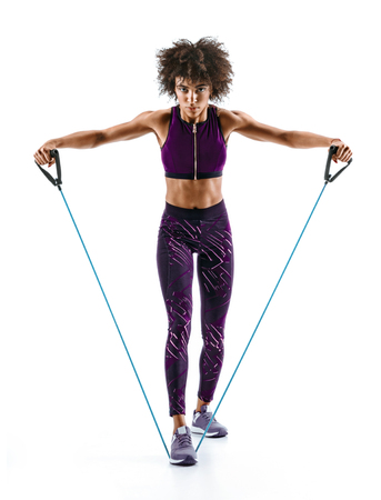 Sporty young girl using resistance band doing lateral raise. Photo of african girl in silhouette on white background. Strength and motivation