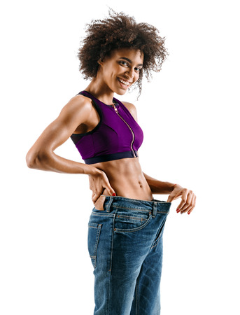 Young girl delighted with her dieting results. Photo of young african girl isolated on white background. Strength and motivation