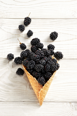 Blackberry explosion. Photo of in waffle cone on white wooden table. Top view. High resolution product. Stock Photo