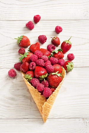 Raspberry and strawberry explosion. Photo of raspberry and strawberry in waffle cone on white wooden table. Top view. High resolution product.
